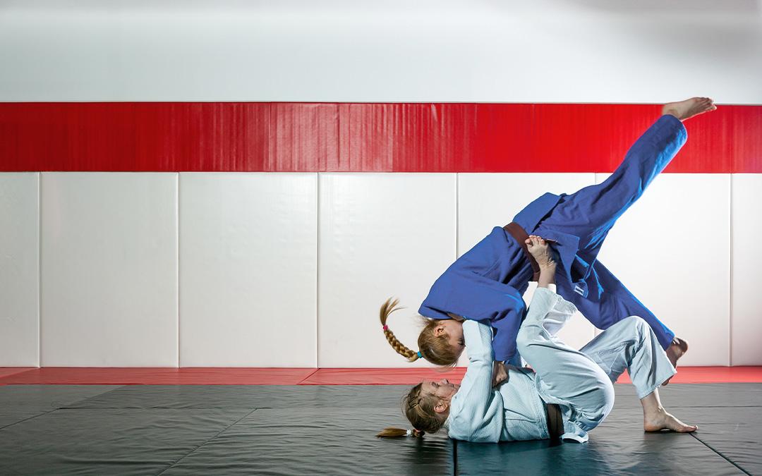 Zwei Frauen beim einer Judoübung auf Bodenmatten