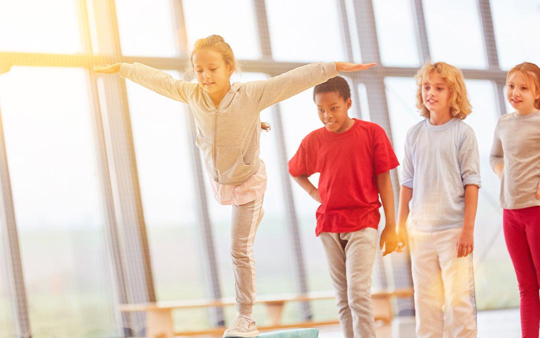 Mädchen mit Gymnastik Übung auf dem Schwebebalken