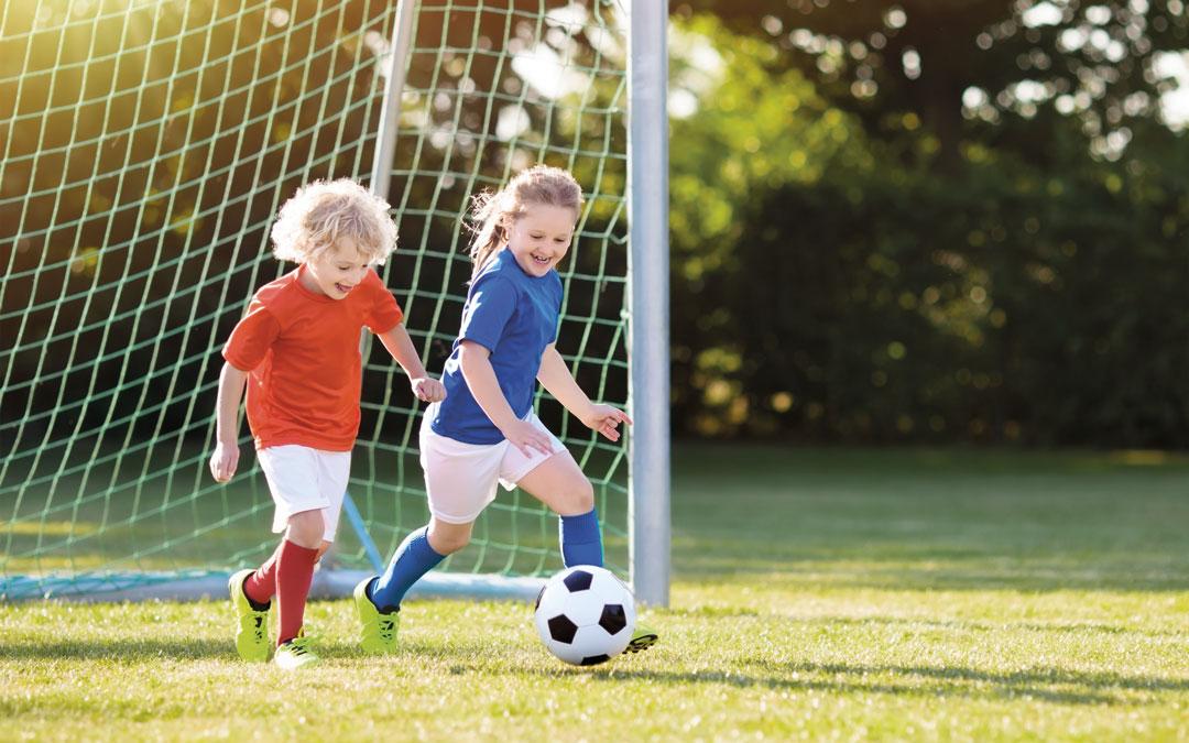 Zwei Kinder spielen Fussball